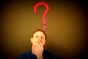 Image of a person standing in front of a wall with a question mark behind him