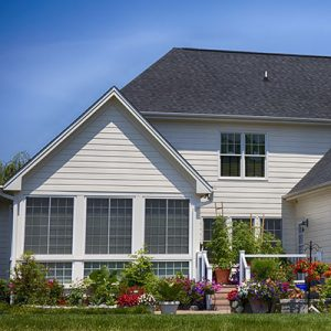 Exterior-of-white-painted-home-in-summer-with-flowers