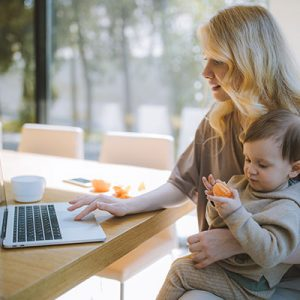 woman-holding-baby-and-on-computer