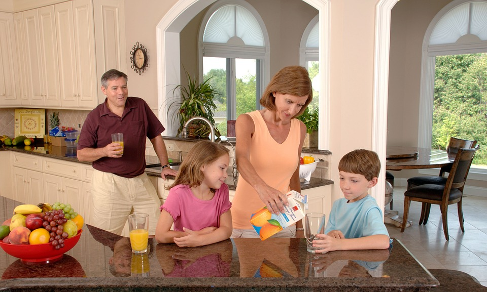 family-drinking-orange-juice-in-kitchen