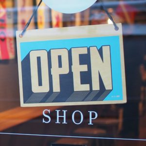"""Baby blue """"Open"""" sign hanging on a glass storefront door."""