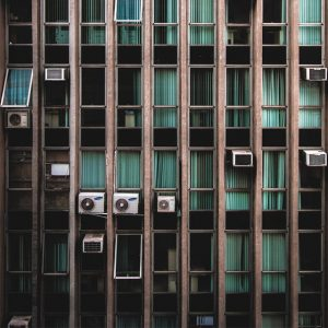 Outdoor view of AC units in windows of an apartment building