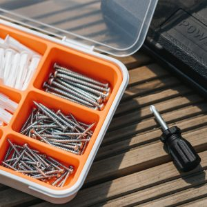 Tool box with screws and a short handle phillips head screwdriver.