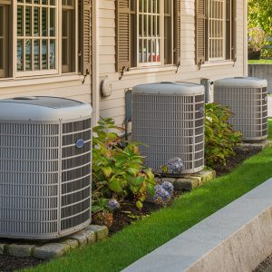 Commercial HVAC units outside next to a sidewalk.
